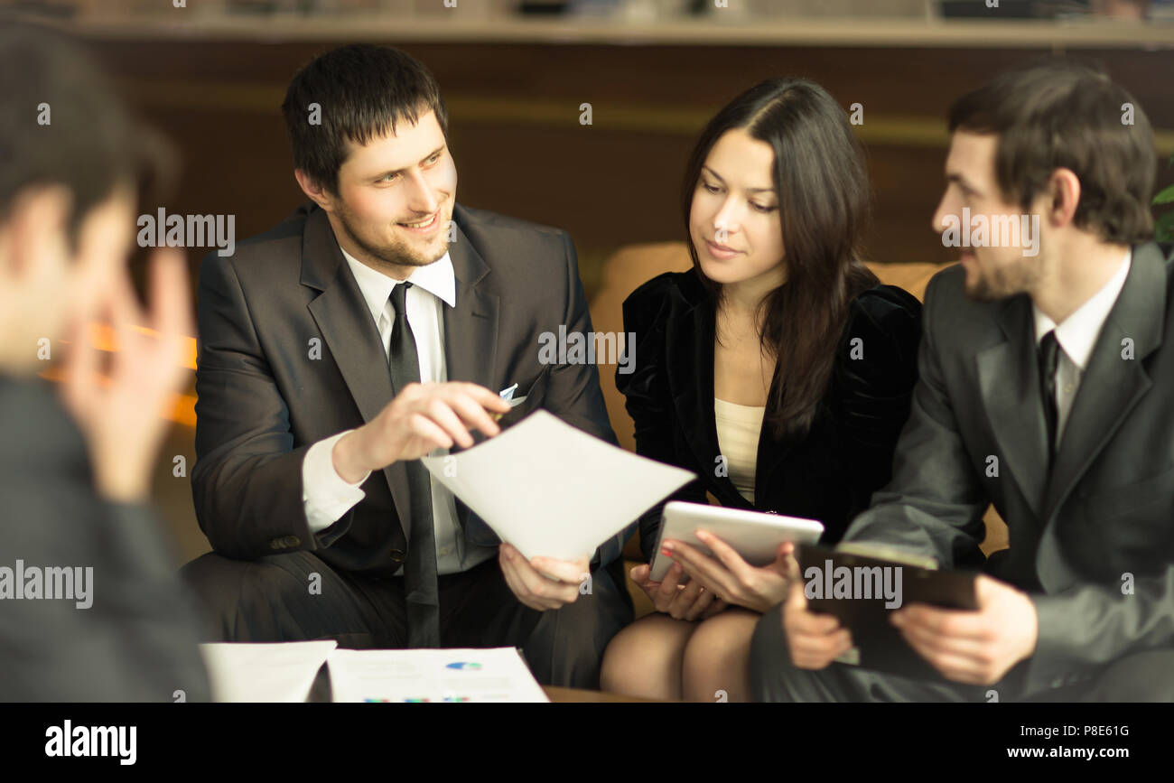group of successful businessmen. Discussion of an important aspect in the office - Stock Image