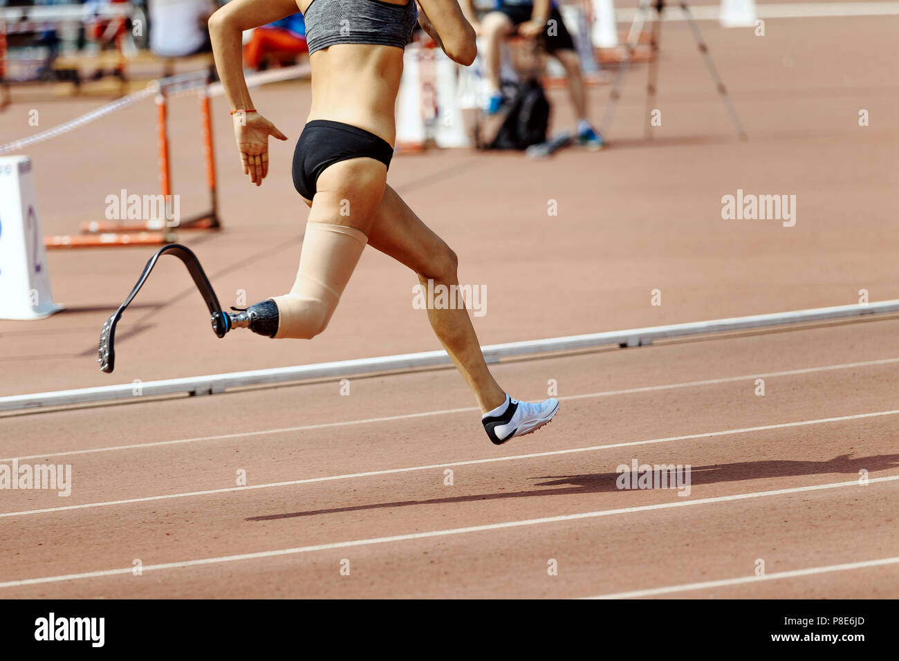 8ac8223585ecf8 woman runner disabled athlete on prosthesis leg running in track - Stock  Image