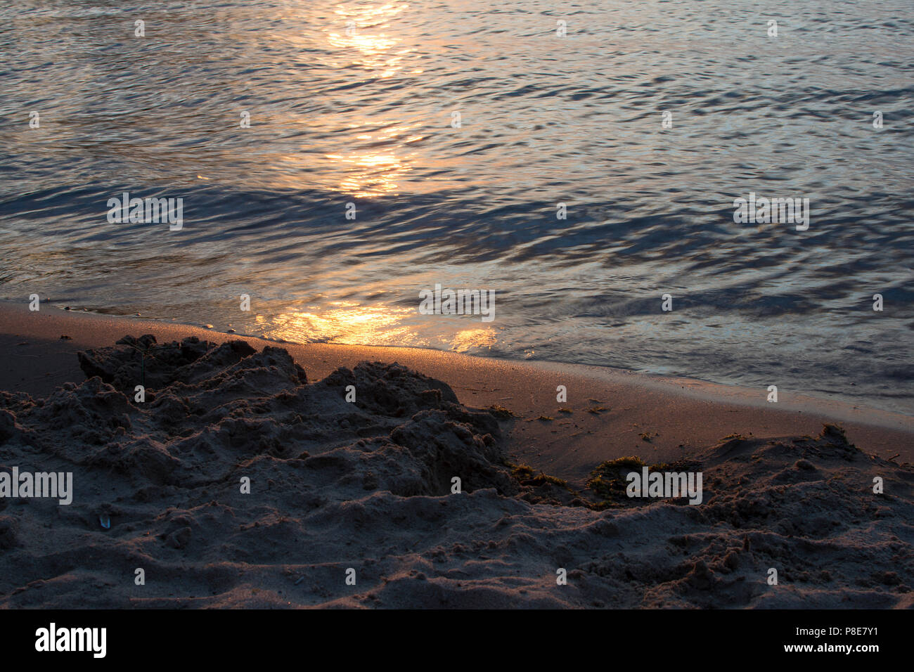 Closeup of glimmering sand on beach with reflection of the sun in the water. - Stock Image