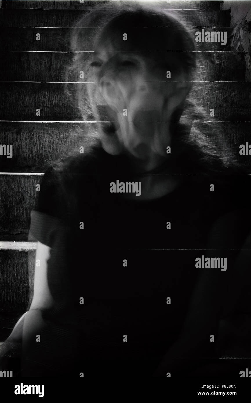 Dark, black and white, rough image of unrecognizable woman in motion blur screaming. - Stock Image