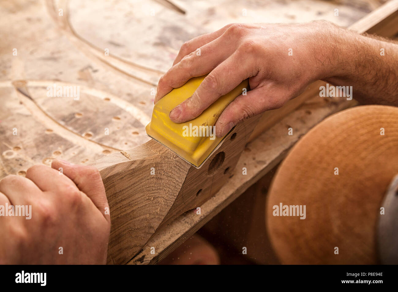 Experienced carpenter in work clothes and small buiness owner working in woodwork workshop,  using sandpaper for polishing children's helicopter blade Stock Photo