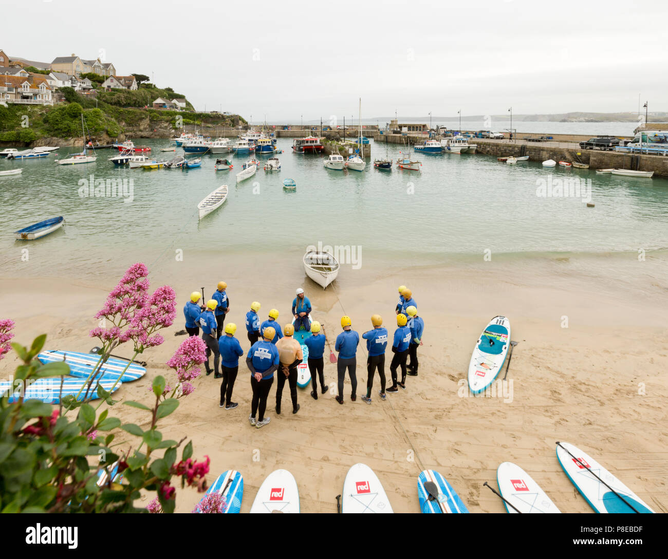 Newquay Cornwall June 2018. Board paddle surfer lessons at Newquay Harbour, Cornwall. Unsharpened. - Stock Image