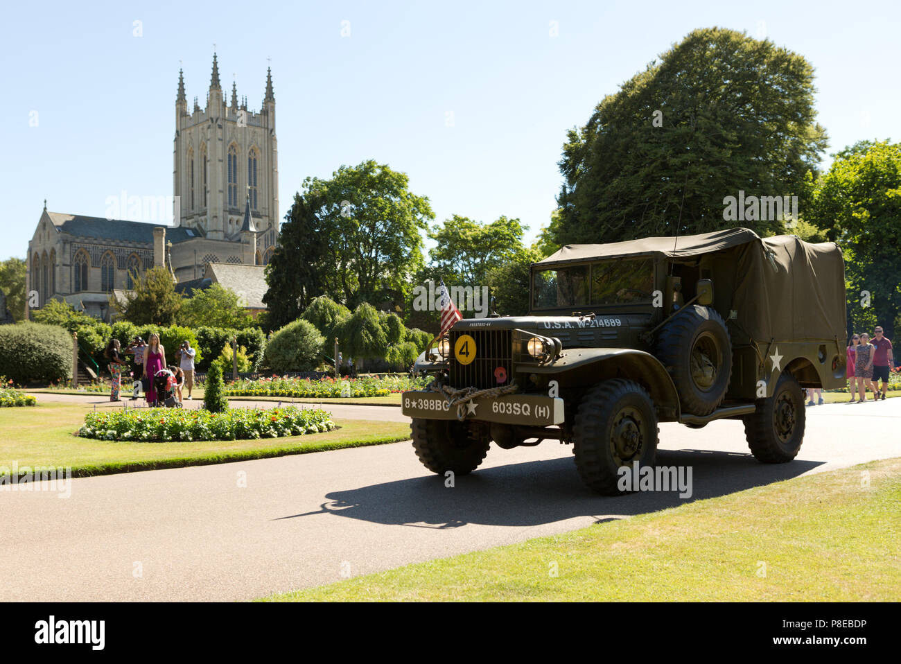 US Army truck driving through Abbey Gardens, Bury St Edmunds during Armed Forces Day with St Edmundsbury Cathedral in background. Unsharpened - Stock Image