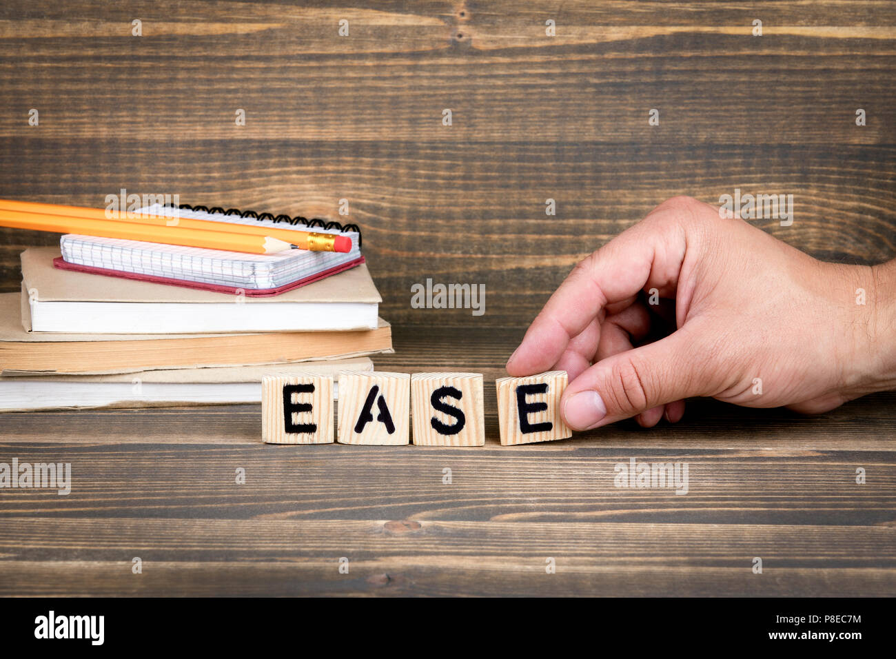 Ease. Wooden letters on the office desk - Stock Image