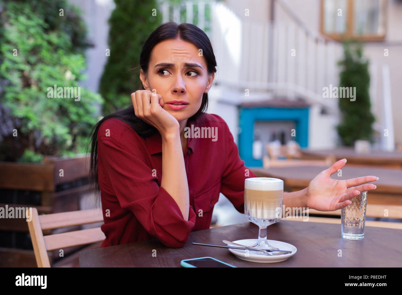 Businesswoman feeling emotional while having dispute with partner - Stock Image