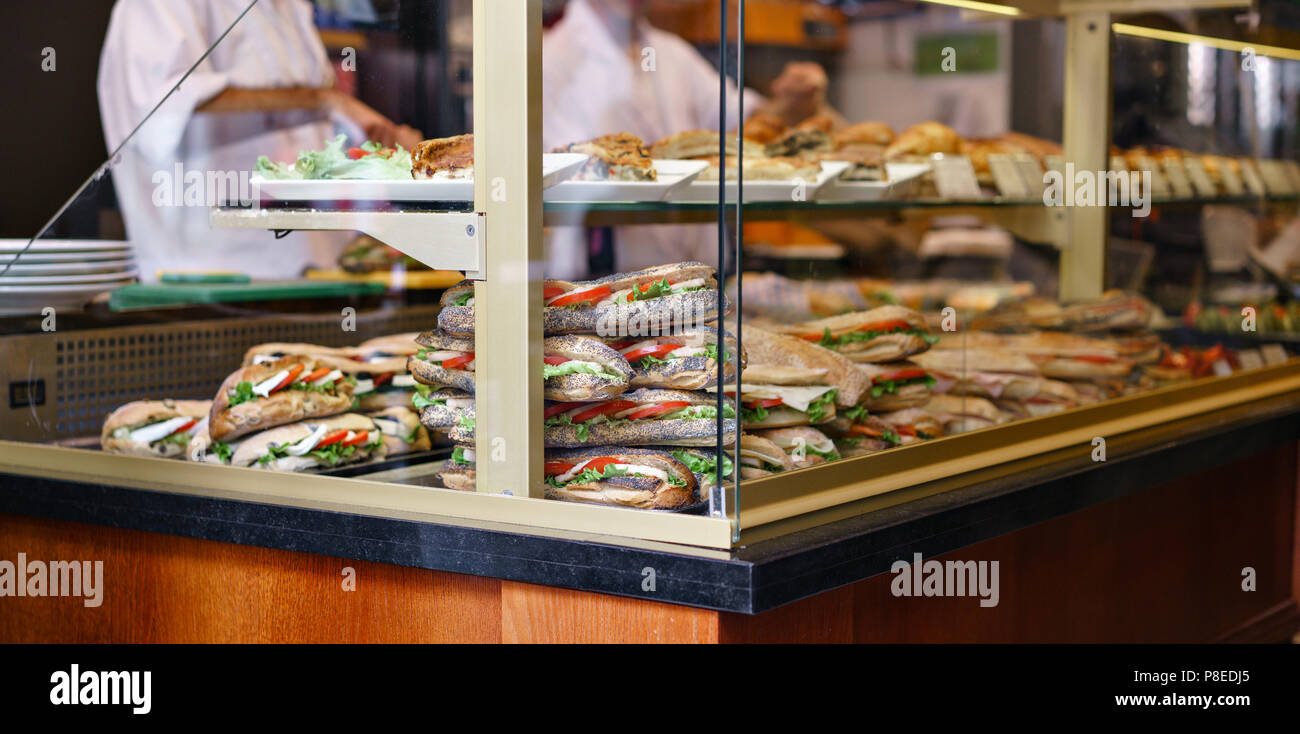 Croissant with ham and cheese. Hot pastries lie on the shelf in the cafe. Buns and bagels in the store. - Stock Image
