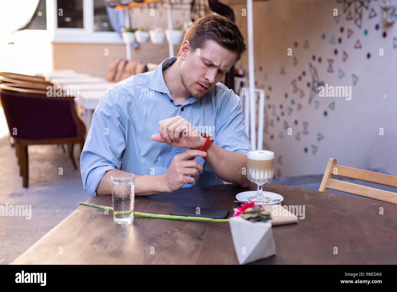 Handsome man looking at his nice red wrist watch - Stock Image
