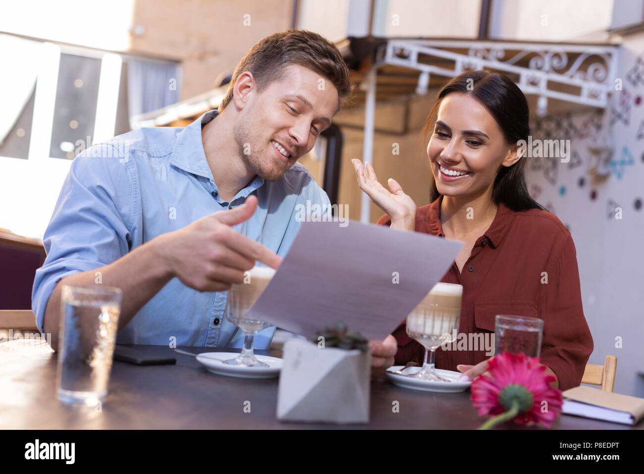 Two loving beaming personalities reading congratulation letter - Stock Image