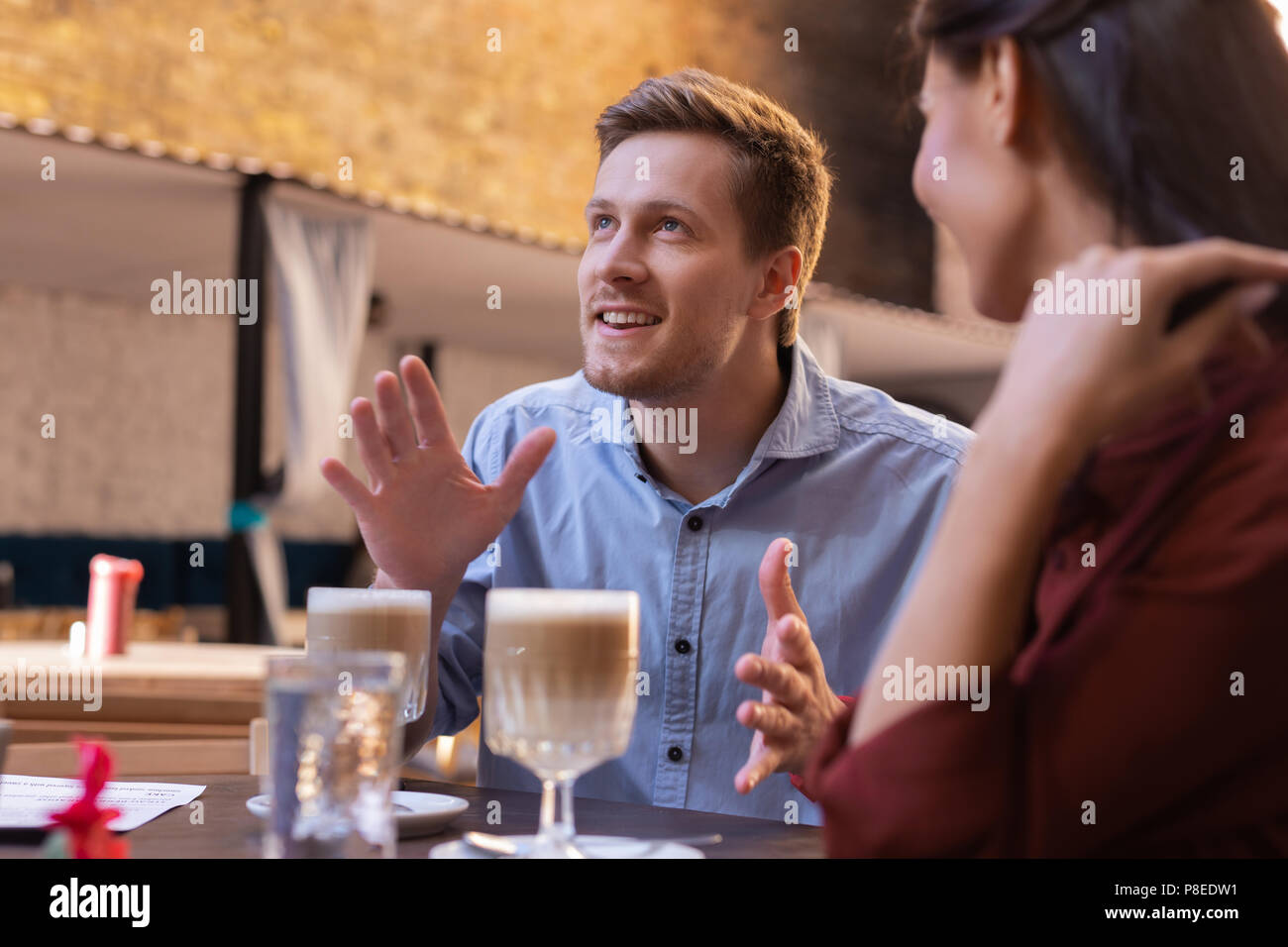 Blue-eyed man feeling amazed while communicating with girlfriend Stock Photo