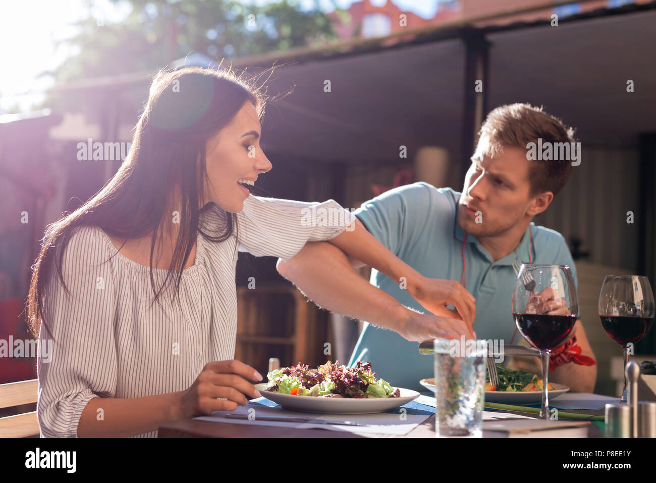 Greedy man not letting his woman trying his salad - Stock Image