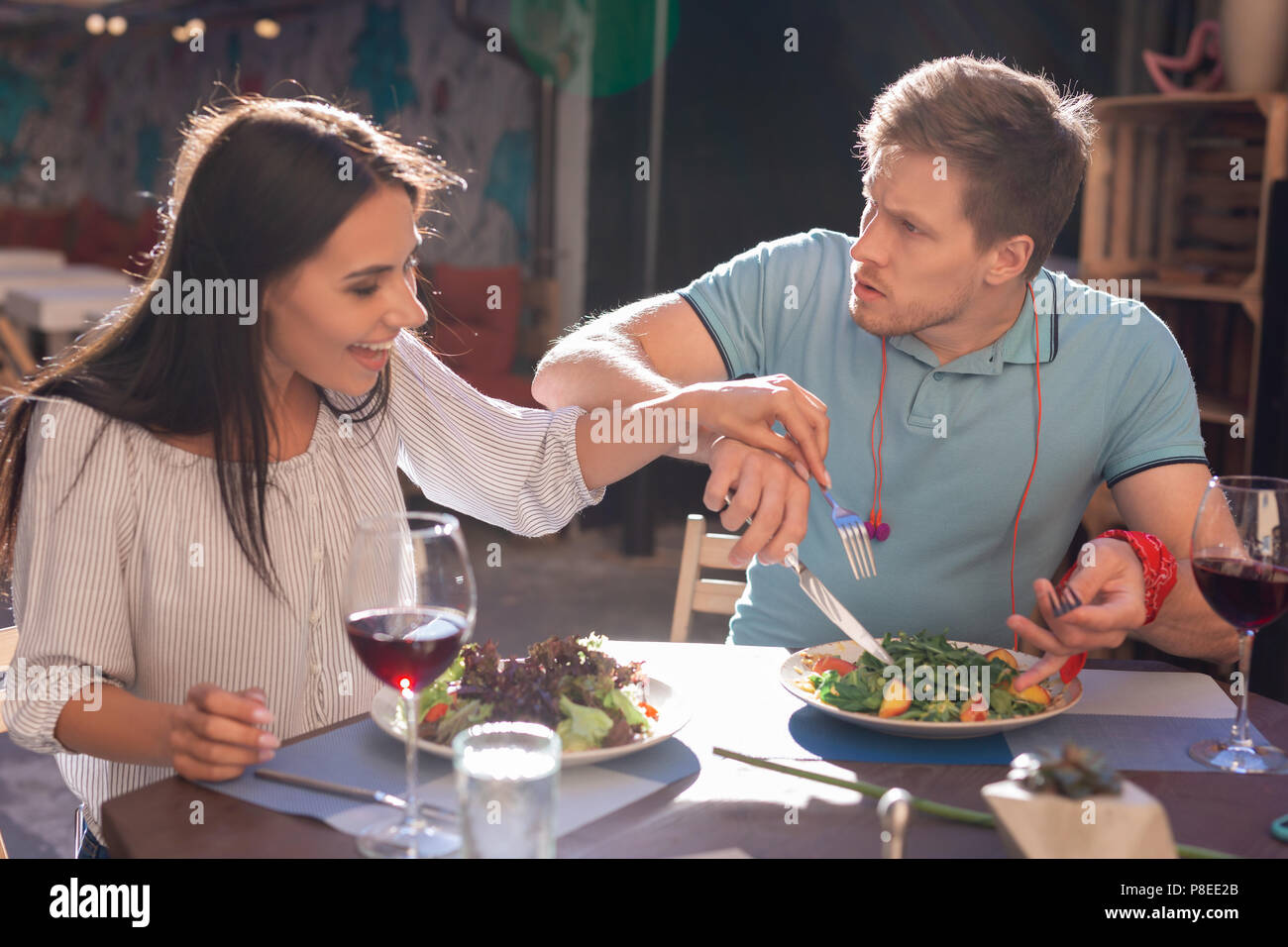 Beaming woman having desire trying some salad of her man - Stock Image