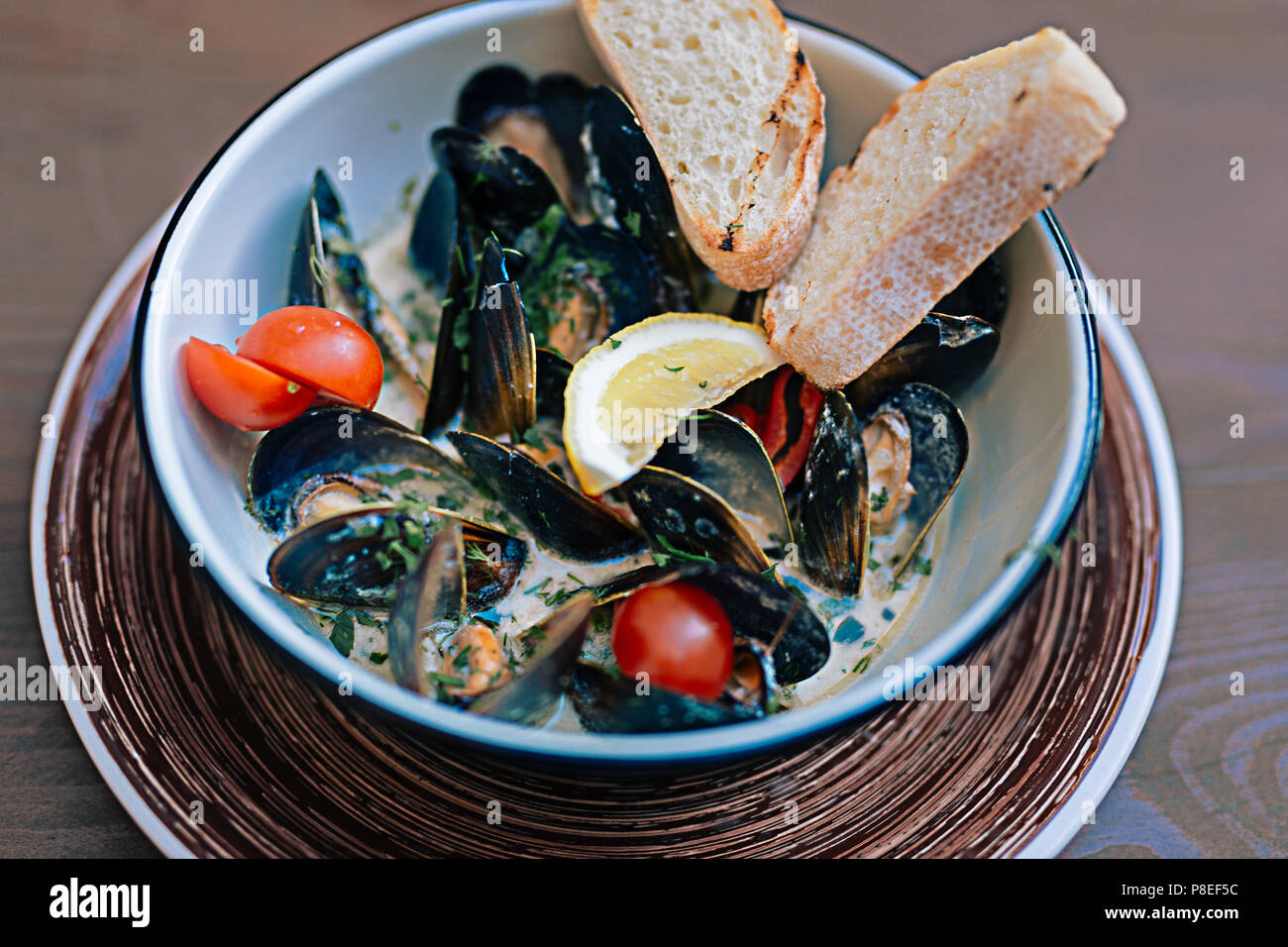 Mussels dish with some bread and little tomatoes Stock Photo