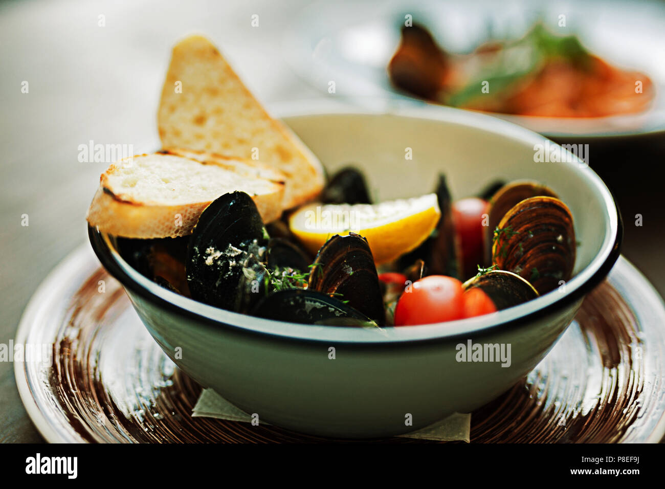Selective focus of fresh mussels in ceramic plate - Stock Image