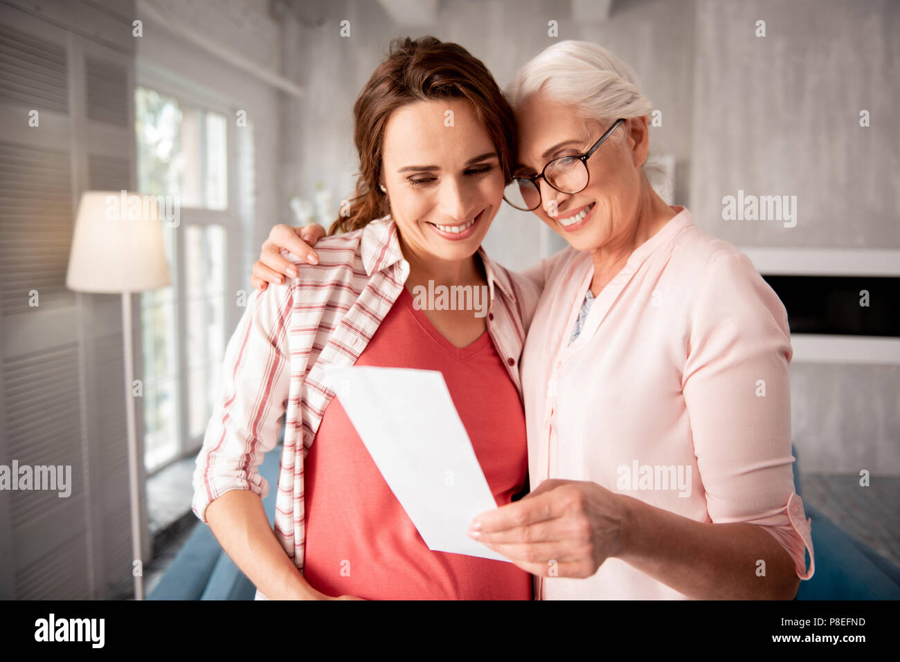 Woman in glasses smiling providing support to her pregnant daughter - Stock Image