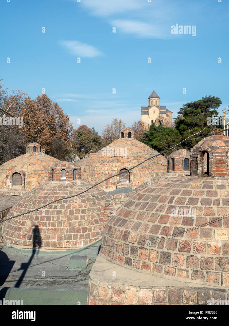 Old dome-shaped bathhouse roofs with Metekhi church in background, Abanotubani district, Tbilisi, Georgia - Stock Image