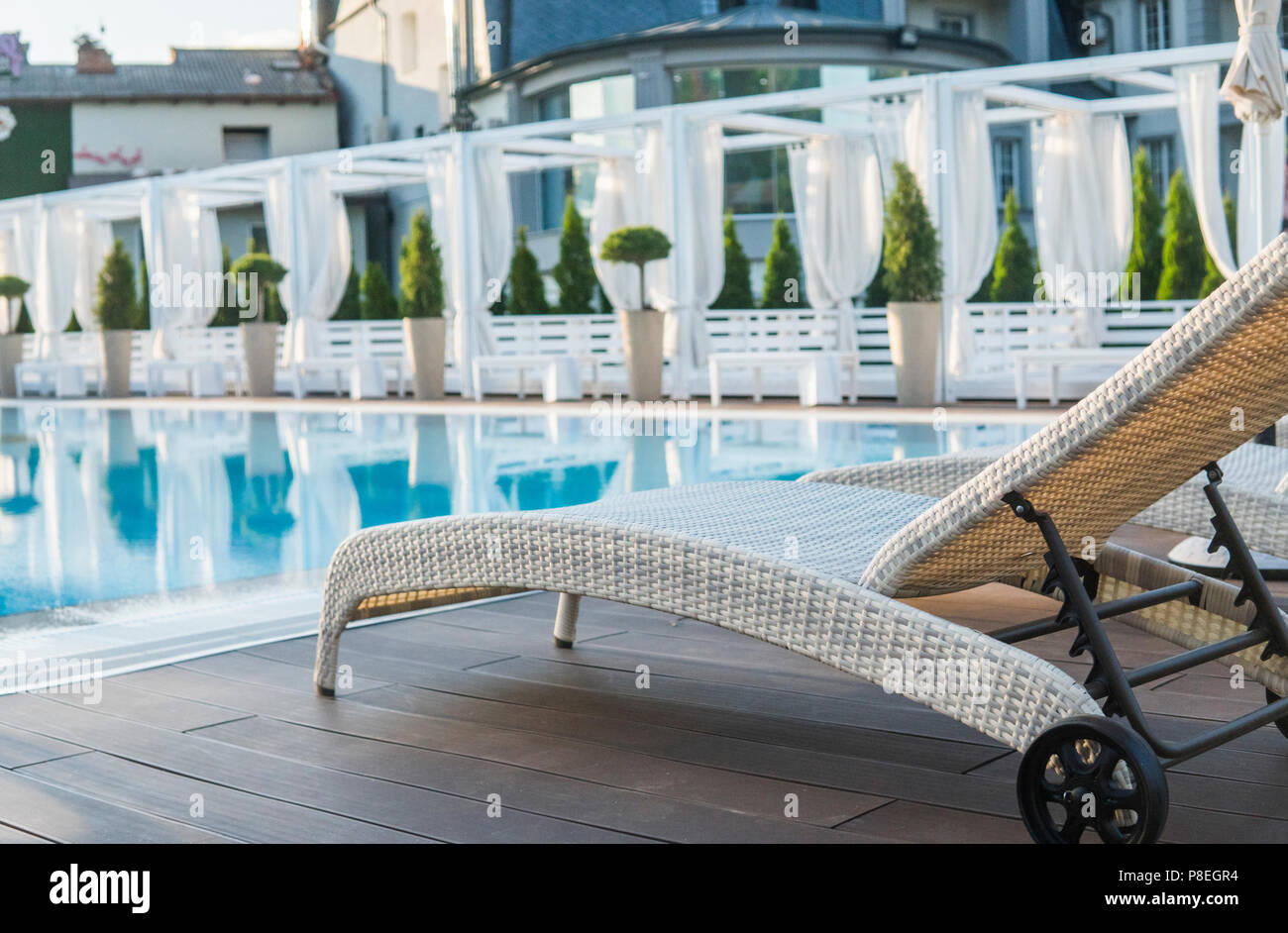 Sunbed near pool with clean water in sunny day. - Stock Image