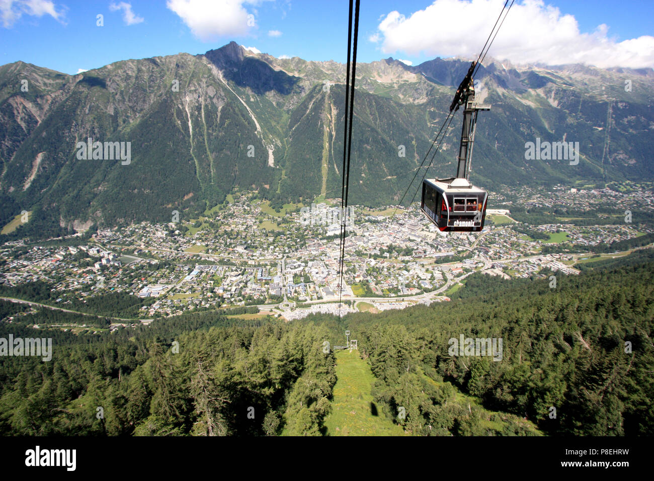 Cable car heading for the peak of the Aiguille-du-Midi in the Mont Blanc massif - Chamonix, France, in the background - Stock Image