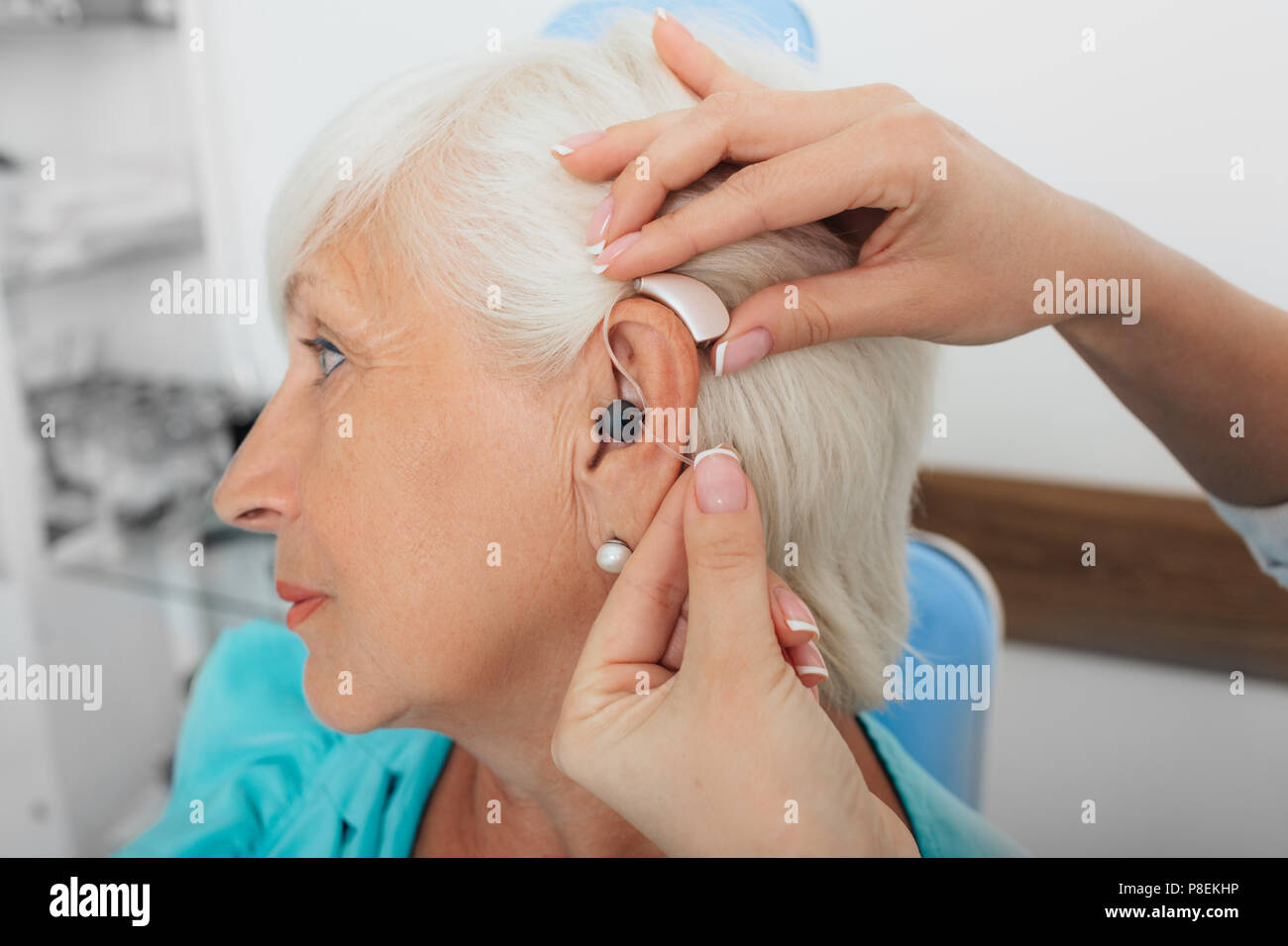adjusting of a hearing aid for an elderly woman - Stock Image