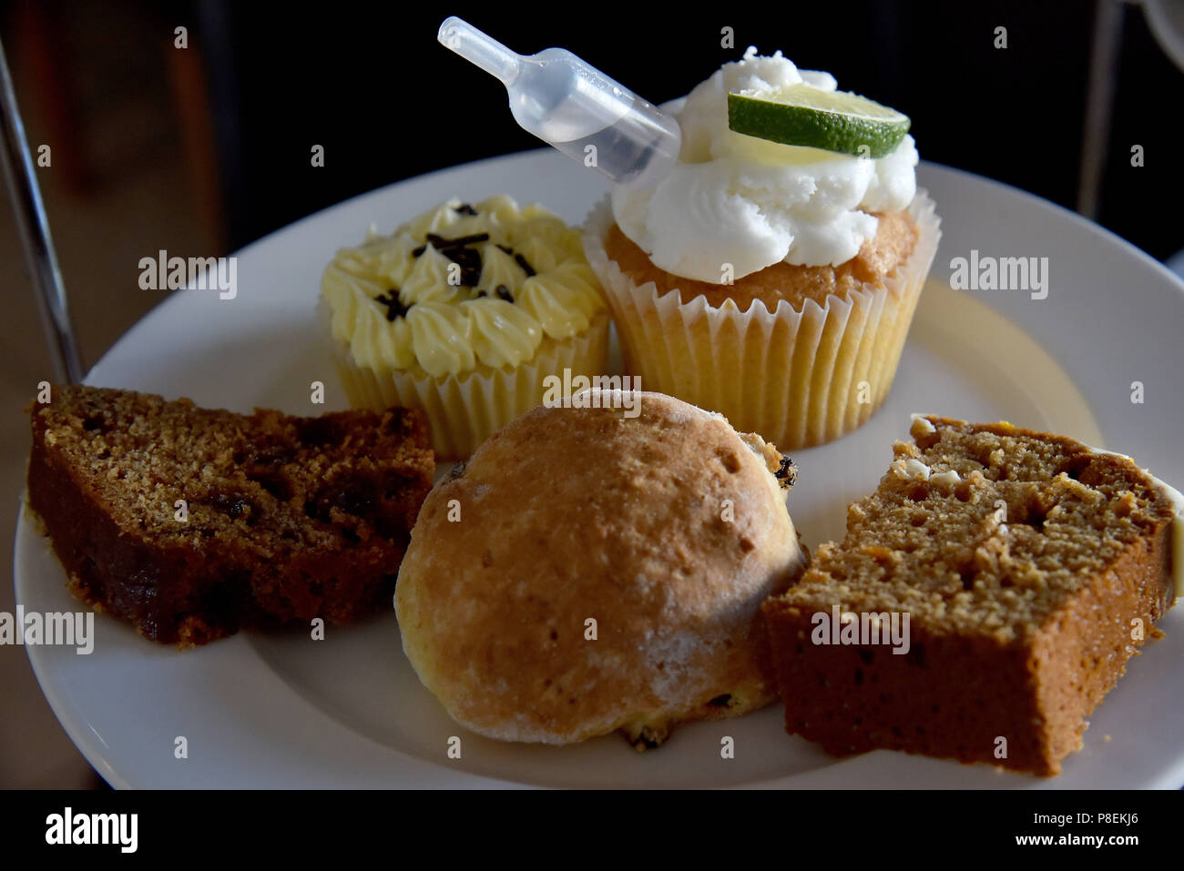 Picture shows a cake stand containing fancy cakes including a cup cake, a scone, date and walnut and a slice of coffee cake - Stock Image