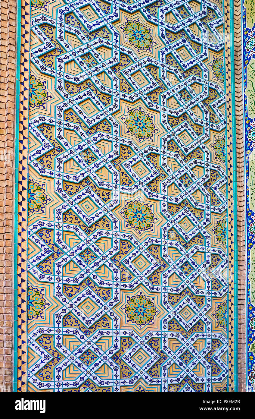 The wall of Safe Azakhane Mosque is covered with intricate Islamic patterns of glazed tiles and relief stellar details, Kerman, Iran. - Stock Image