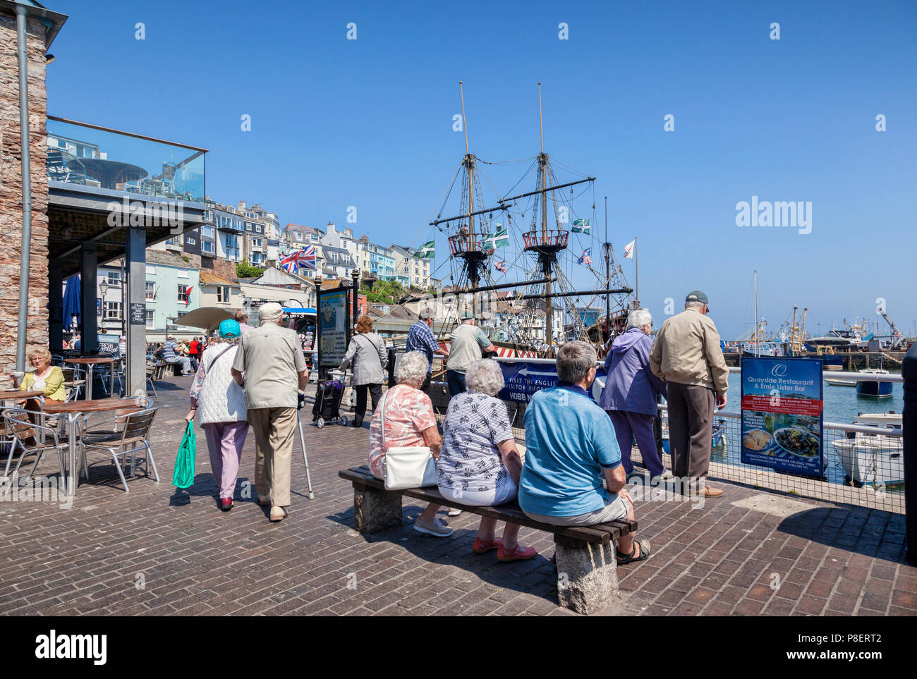 23 May 2018: Brixham, Devon, UK - Senior citizens relaxing on the seafront at Brixham Harbour, with the replica Golden Hind sailing ship. - Stock Image