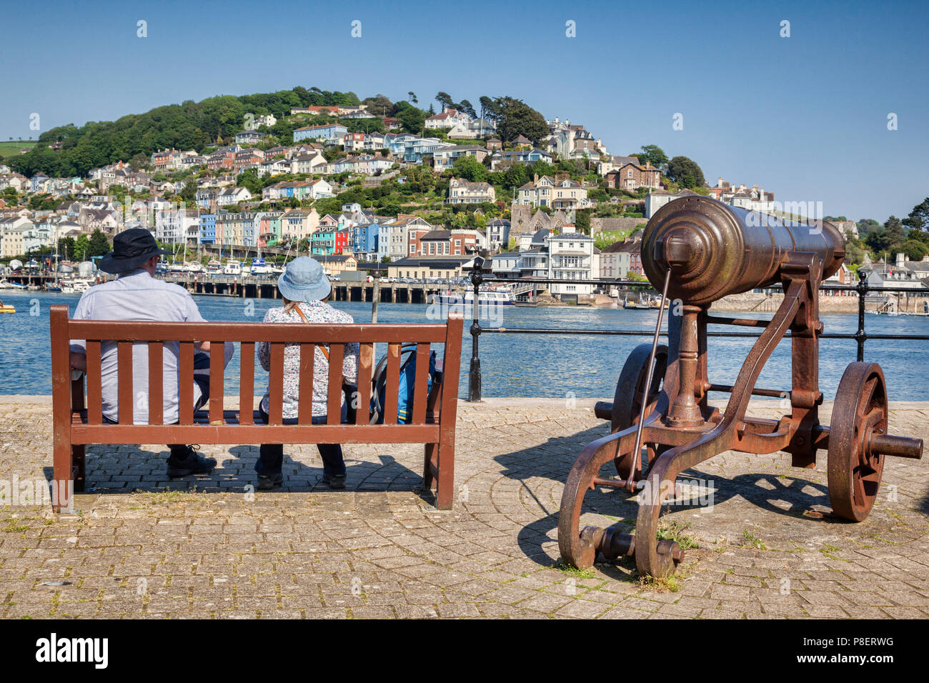 23 May 2018: Dartmouth, Devon, UK - Couple sitting on a bench beside an old cannon, looking out over the River Dart. - Stock Image