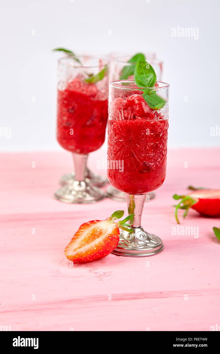 Summer refreshing strawberry sorbet, slush granita drink in serving glasses. Healthy low calorie summer treat, dessert. Iced Cocktail on pink backgrou - Stock Image