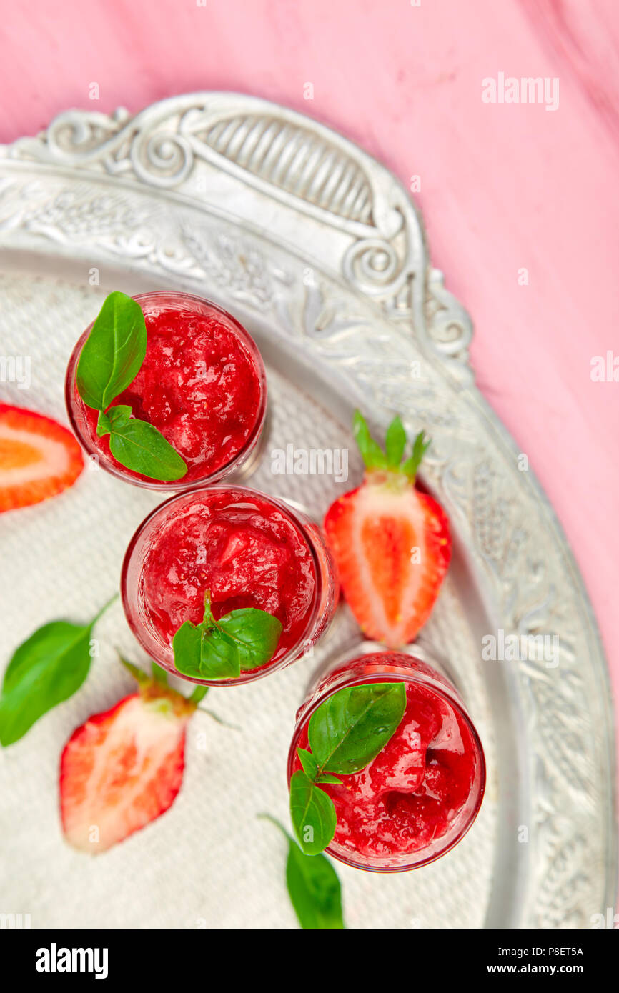 Summer refreshing strawberry sorbet, slush granita drink in serving glasses on silver tray. Healthy low calorie summer treat, dessert. Iced Cocktail o - Stock Image