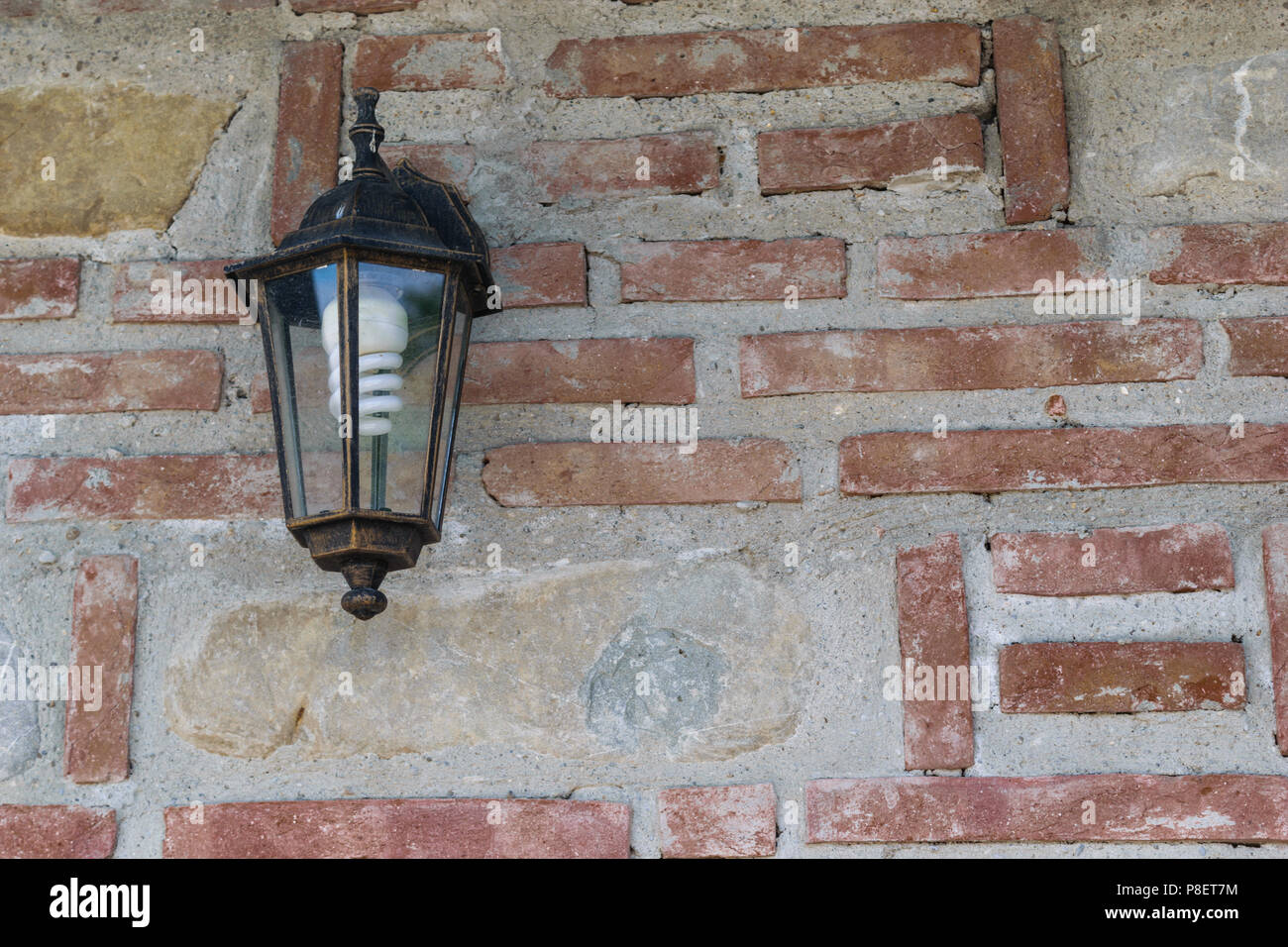 exterior light fixture mounted on brick wall with copy space. Energy saving light bulb installed. - Stock Image