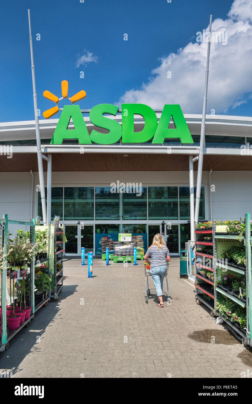 28 May 2018: Newton Abbot, Devon, UK - Asda supermarket entrance, with a woman pushing a trolley towards it. Stock Photo