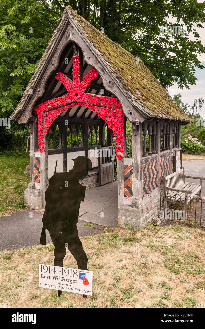 Church of St Mary Magdalene, Eardisley, Herefordshire, UK. Hand-knitted red poppies decorate the lychgate to mark the centenary of the First World War - Stock Image