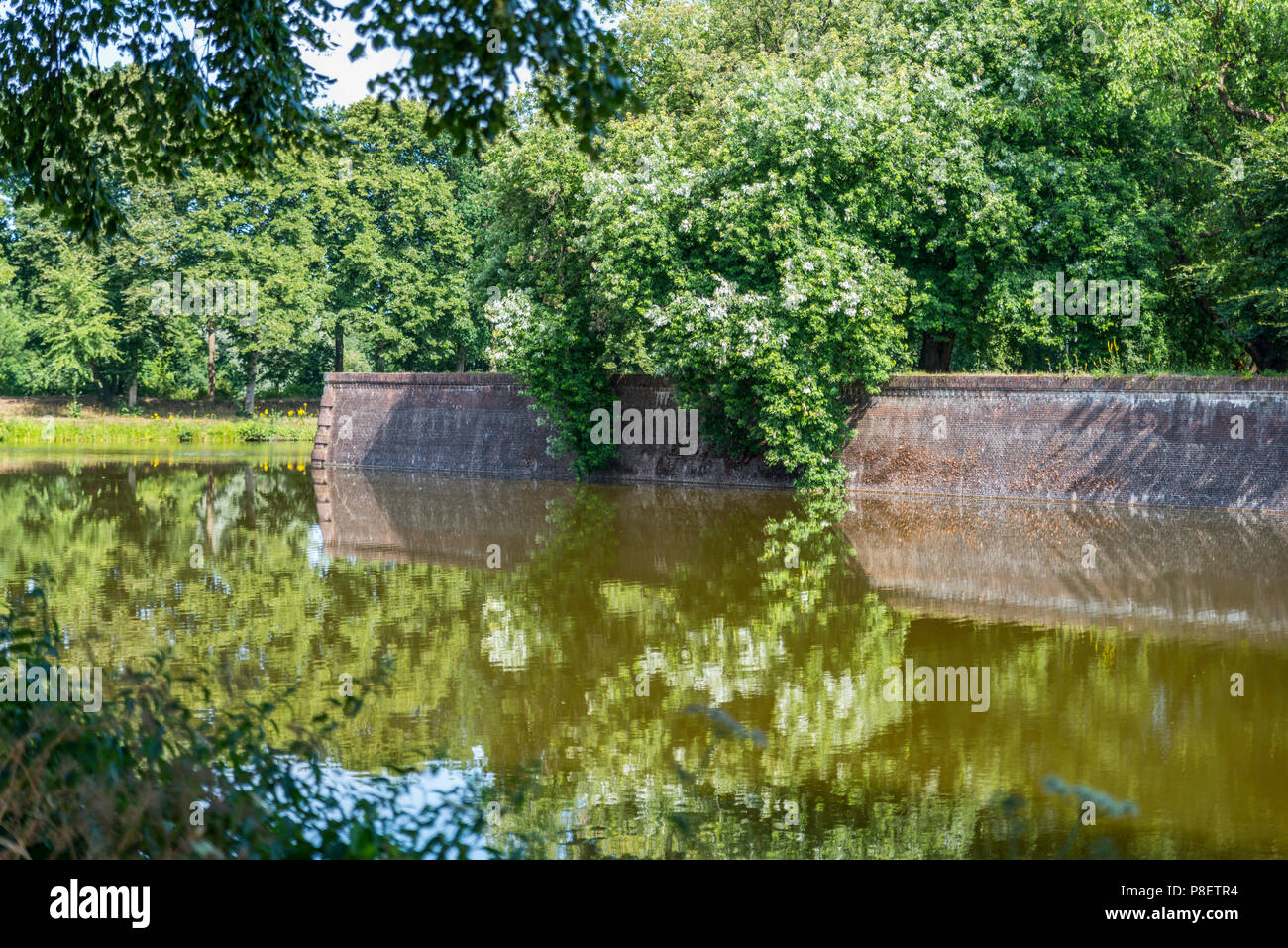 Bastion Oranje the old fortified town of Naarden with reflection of flowers in the water, North Holland, Netherlands, Dutch fortress in water surrounded Naarden Vesting - Stock Image