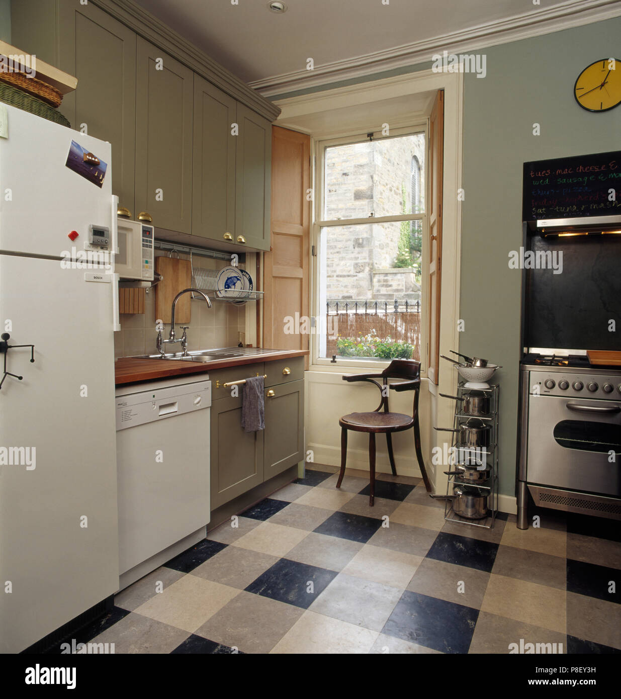 Vinyl chequerboard flooring in a townhouse kitchen with a large fridge freezer - Stock Image