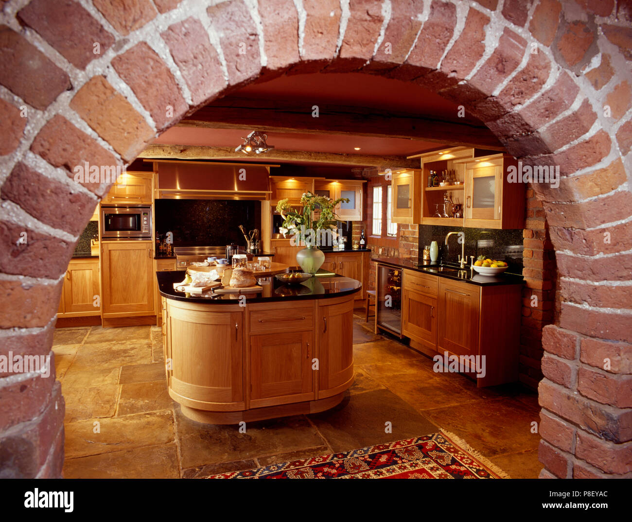 View Through Brick Arch Of Traditional Wooden Kitchen With Oval Island Unit And Stone Flooring Stock Photo Alamy