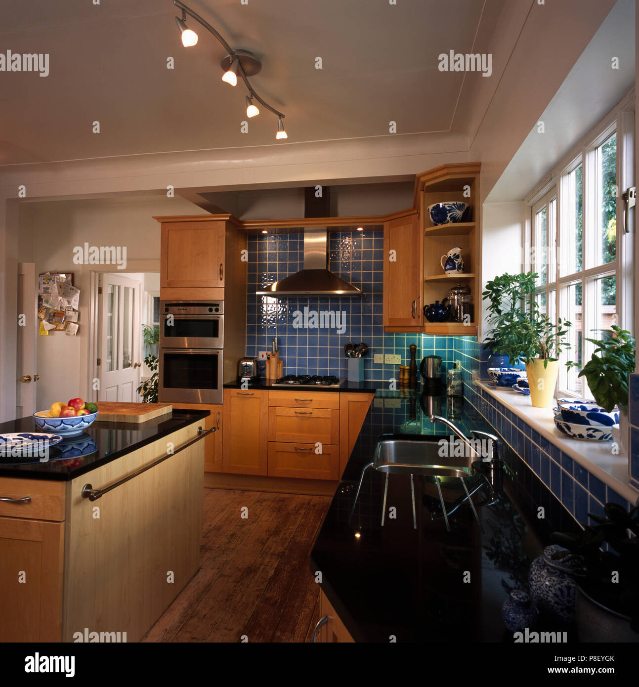 Island Unit And Ceiling Track Lighting In Modern Kitchen With Granite Worktops Stock Photo Alamy