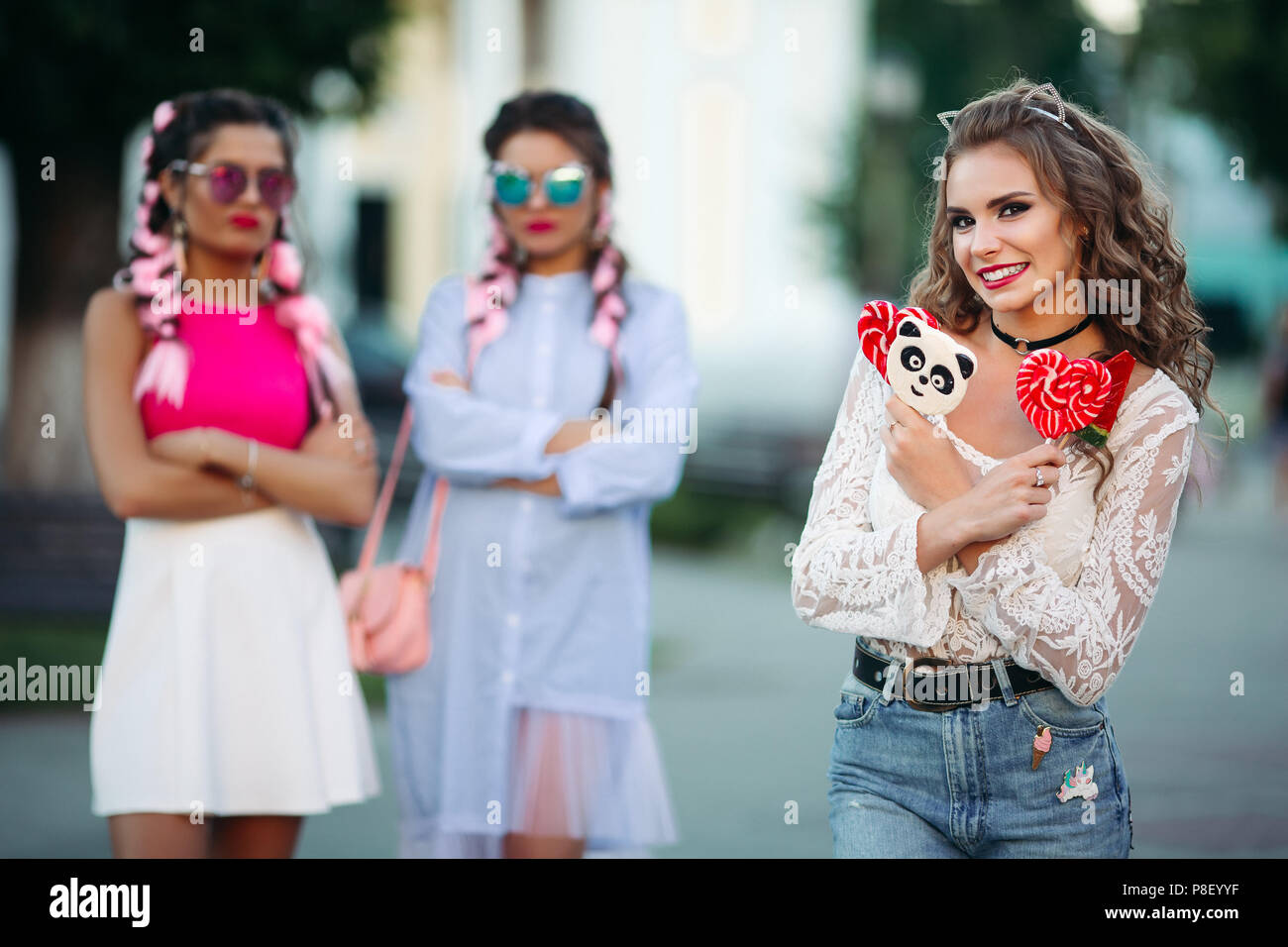 One woman holding colorful candies on stick and smiling, other angry looking. - Stock Image