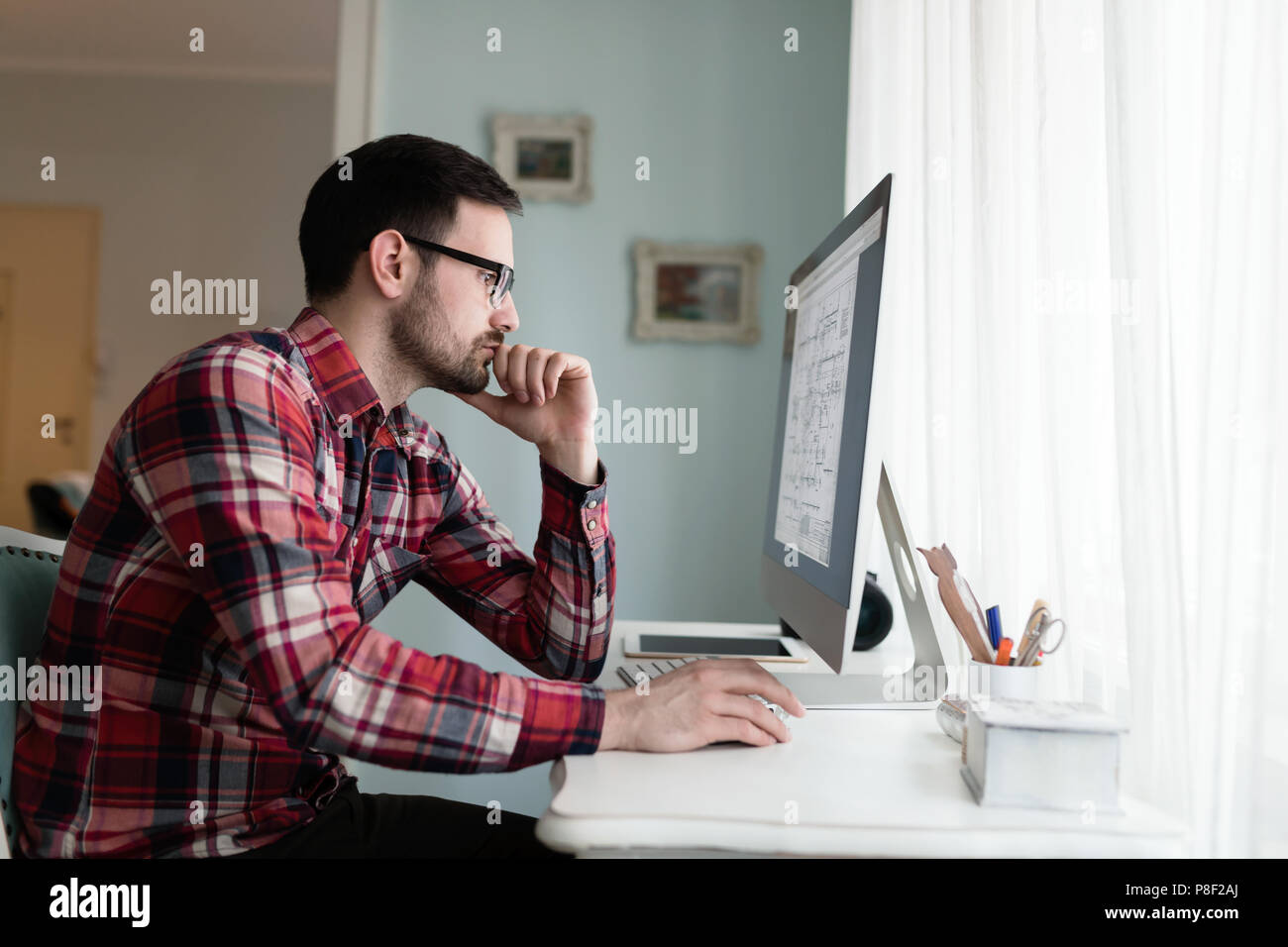 Young designer working on project from home - Stock Image