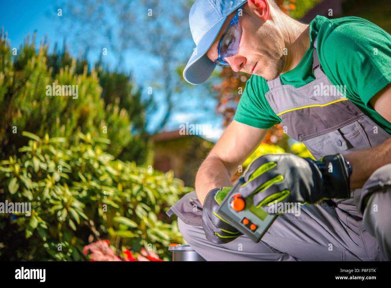 Water Supply Controller in Hand of Professional Garden Technician. - Stock Image