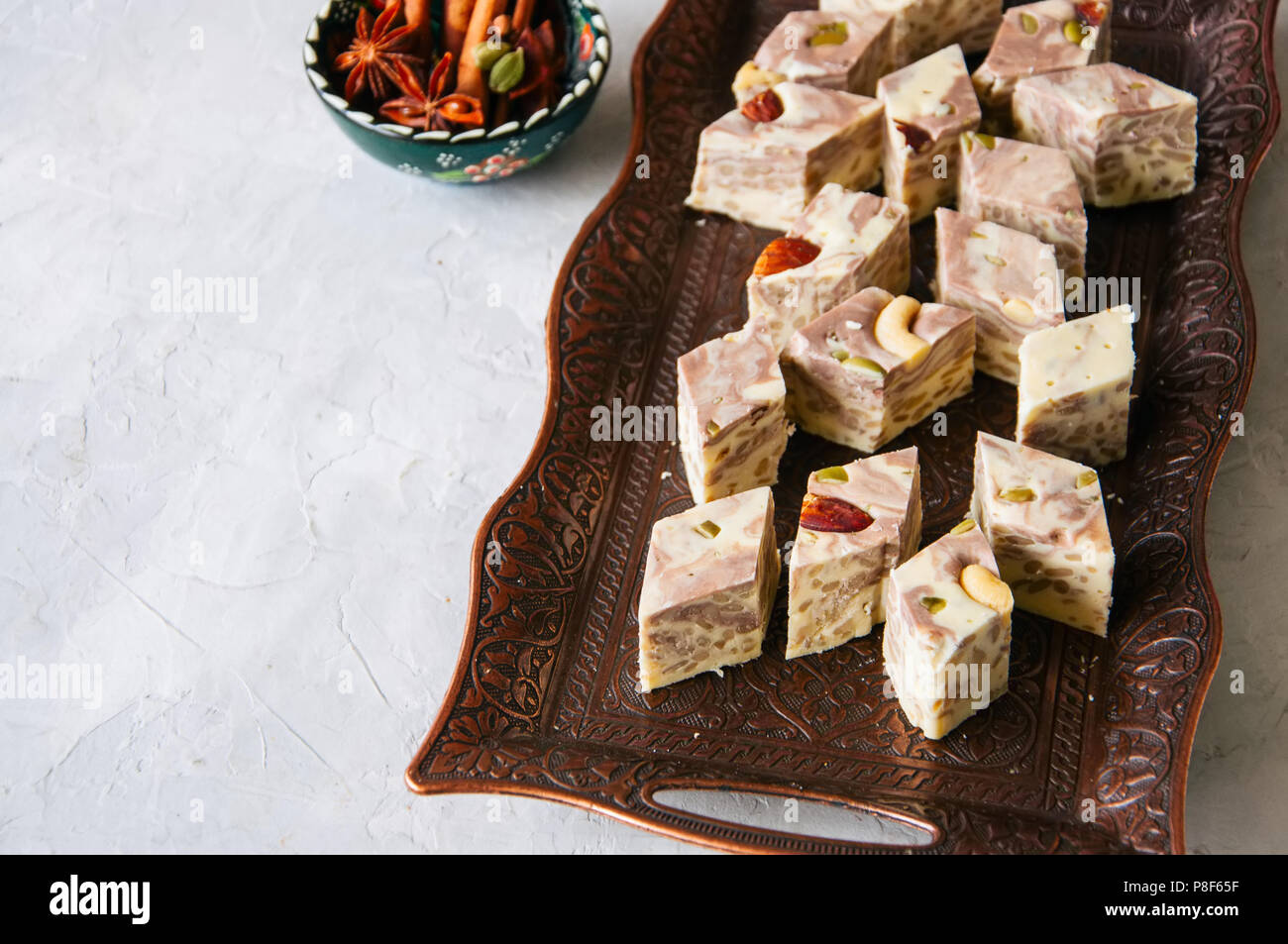 Traditional eastern dessert - halva with nuts and seeds served on a vintage plate. - Stock Image