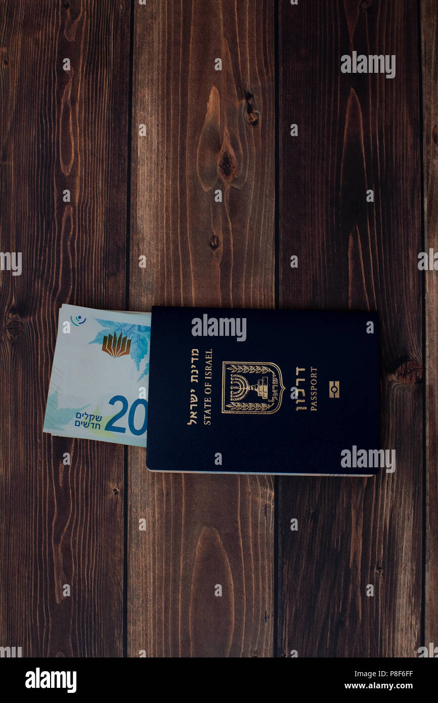 stack of Israeli money bills in the amount of 200 shekels and an Israeli passport on a wooden table Stock Photo