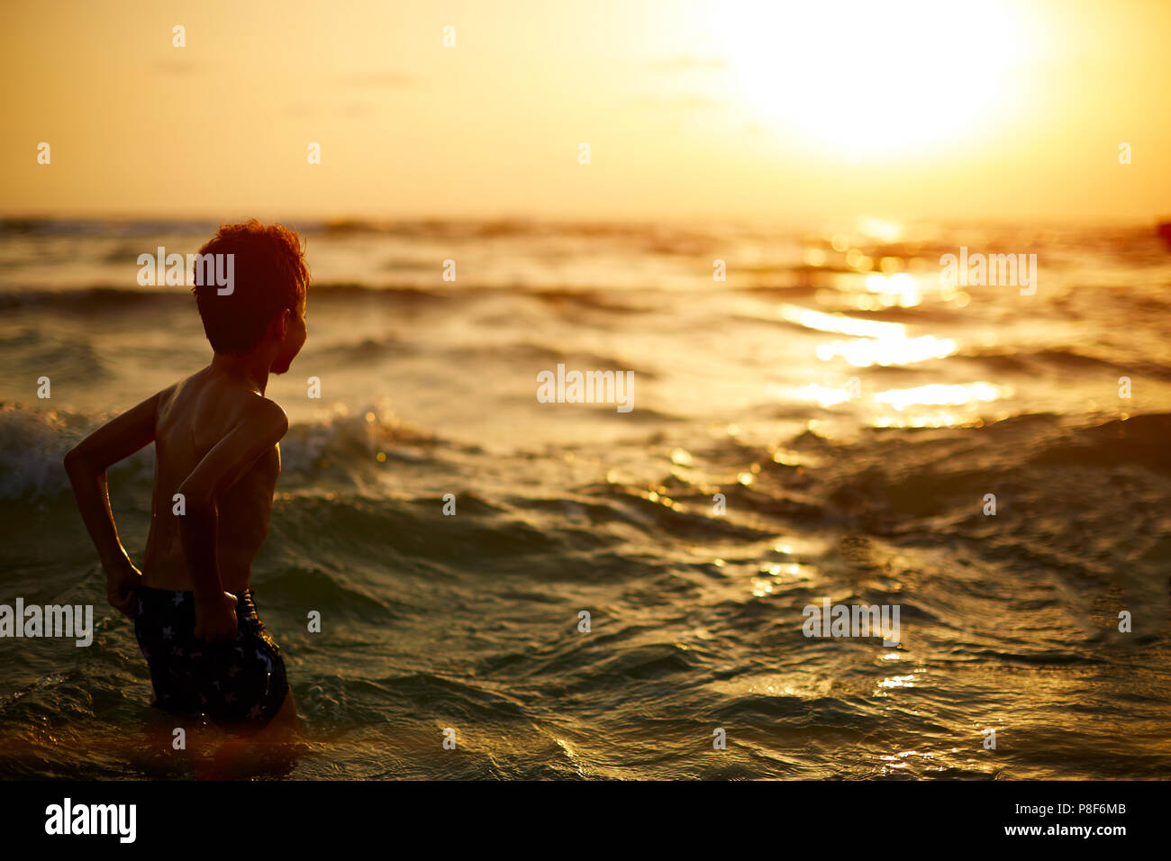 Boy looking out towards the sunset with the waves on there way in. - Stock Image