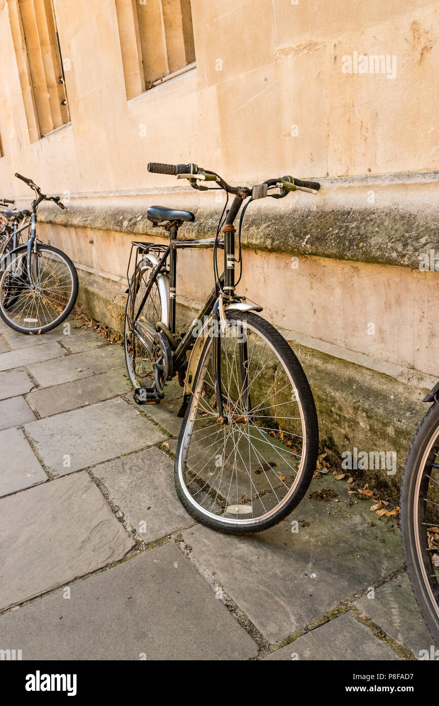 Bicycle with a bent wheel lying against a wall in Oxford city centre. - Stock Image