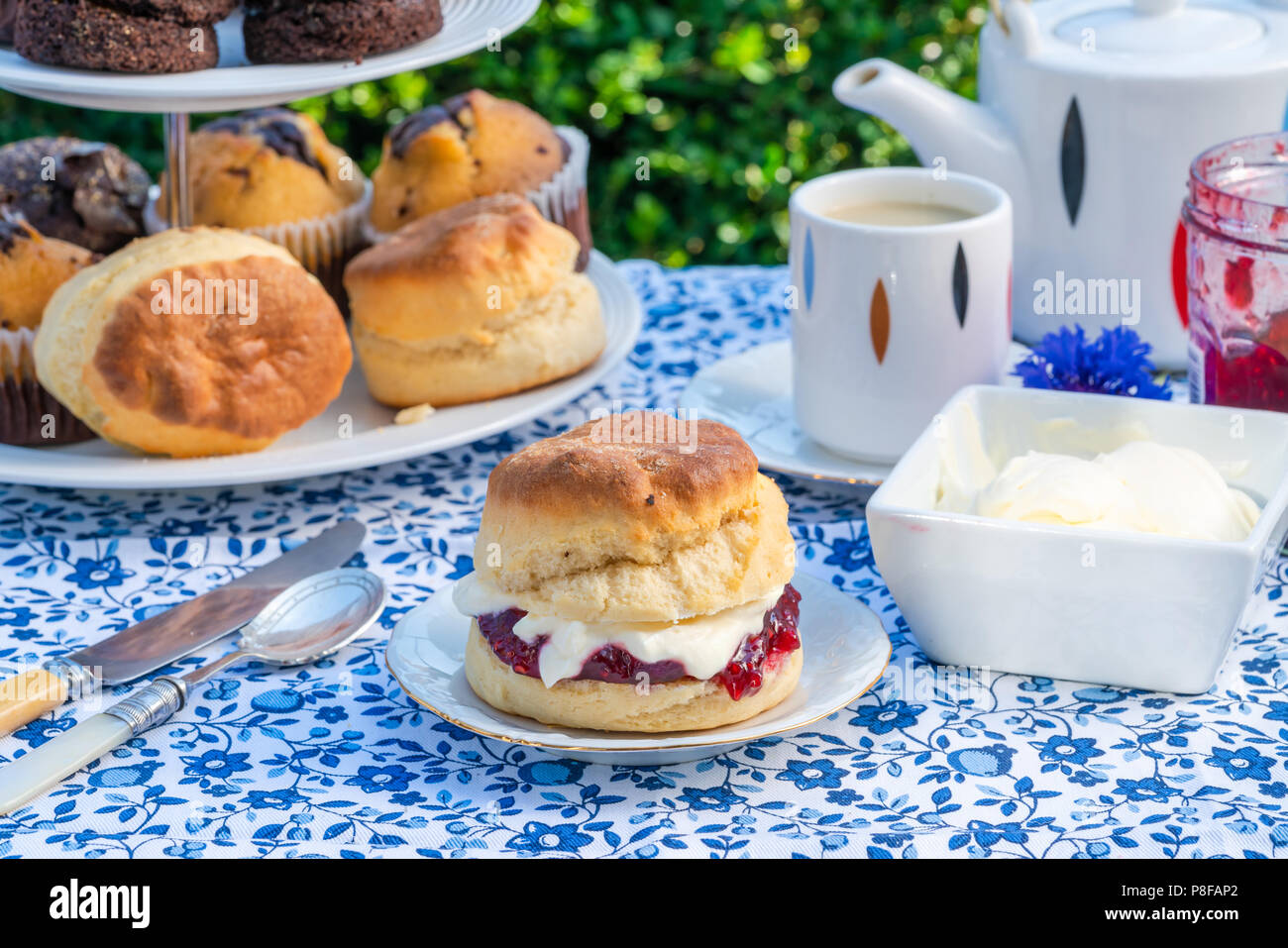 Afternoon tea with cakes and traditional English scones with strawberry jam and clotted cream set up on a table in the garden. Outdoor dining. - Stock Image