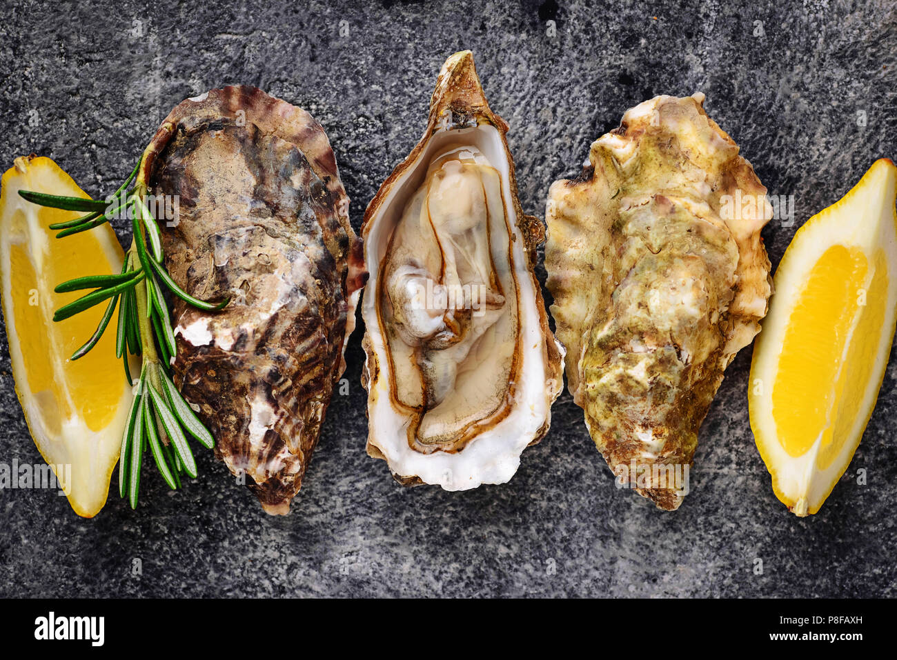 Fresh oysters with lemon and rosemary - Stock Image
