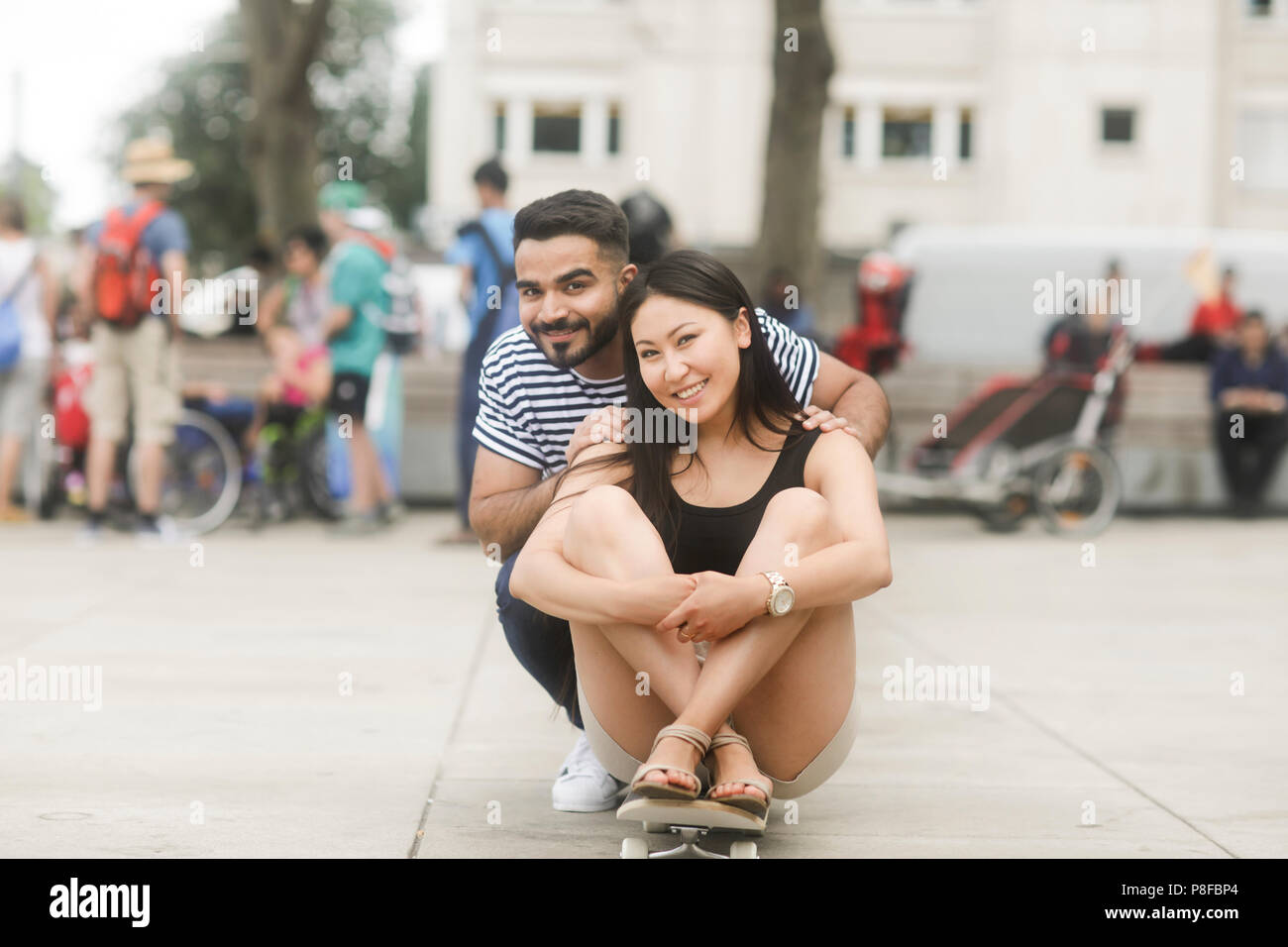 Smiling couple sitting on a skateboard in a city square Stock Photo