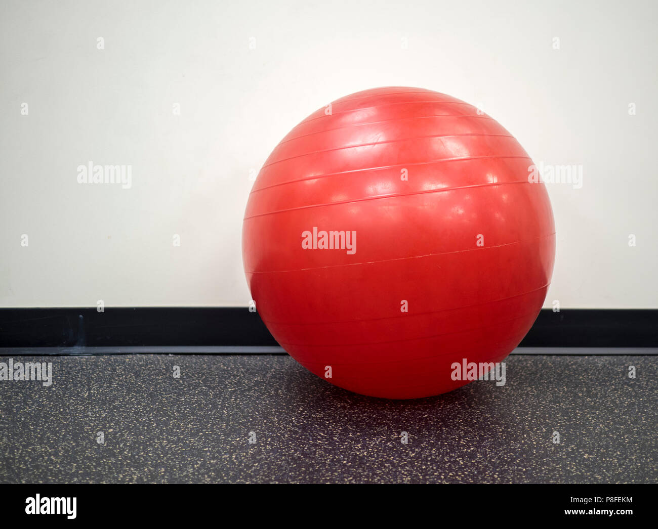 Isolated lone red exercise ball in the gym - Stock Image