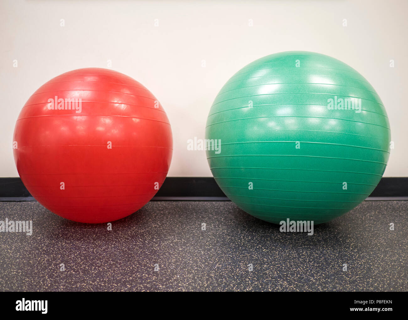 Small red exercise ball beside a medium size swiss ball in the gym - Stock Image