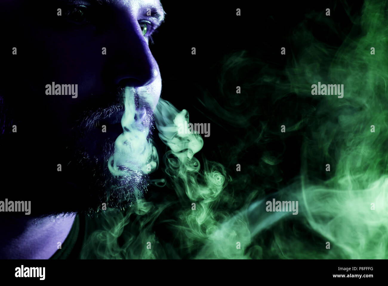 A young man exhales a cloud of colored smoke of blue and green color on a black isolated. Harm to smoking on the example of a young mugger - Stock Image