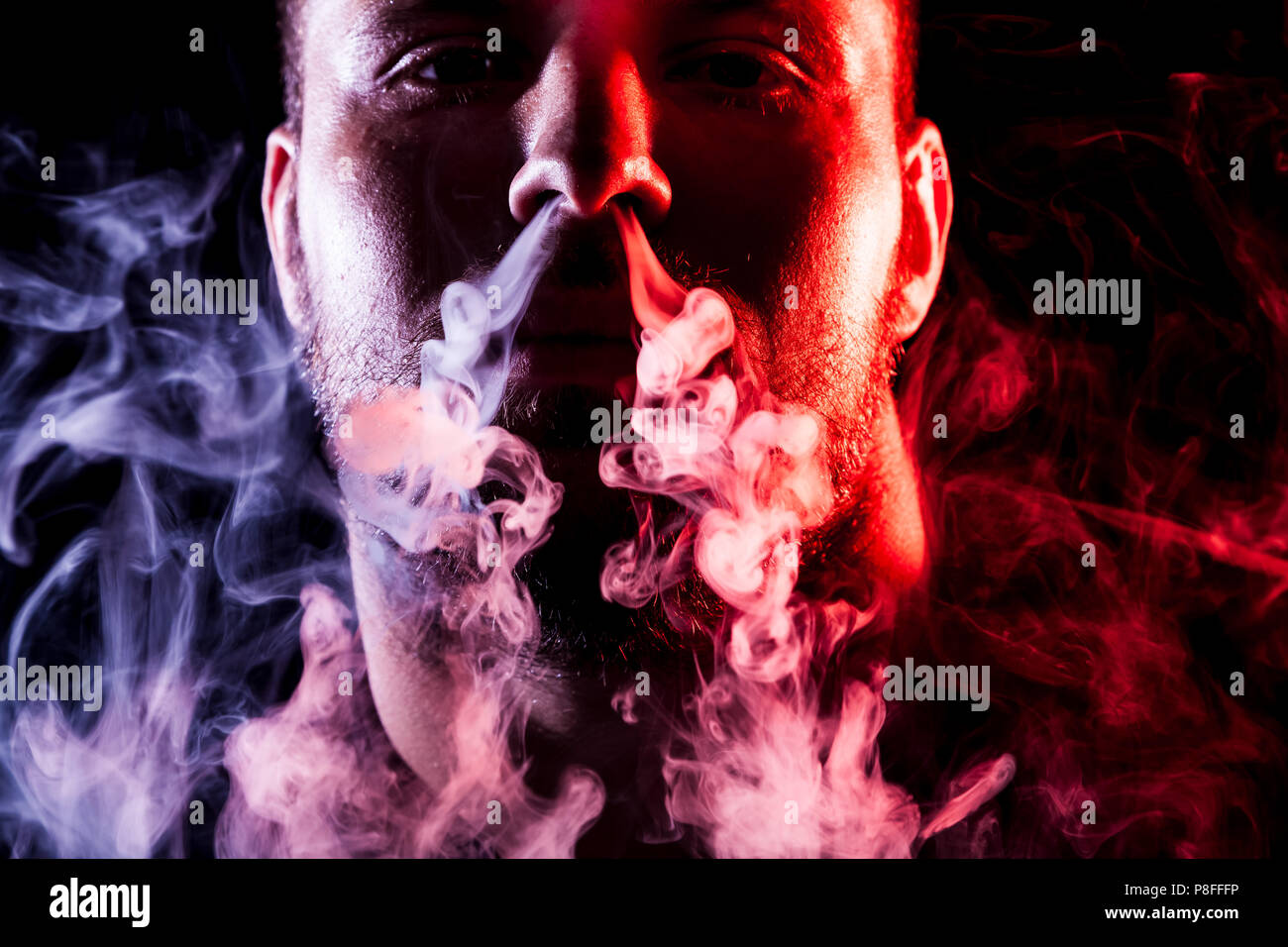 A young man exhales a cloud of colored smoke of red and pink color on a black isolated. Harm to smoking on the example of a young mugger - Stock Image