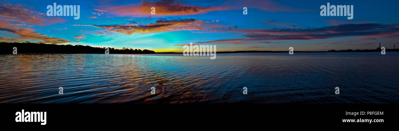 An inspirational panoramic brightly coloured red and blue cloudy tropical sunrise seascape featuring silhouettes with ocean water reflections. - Stock Image